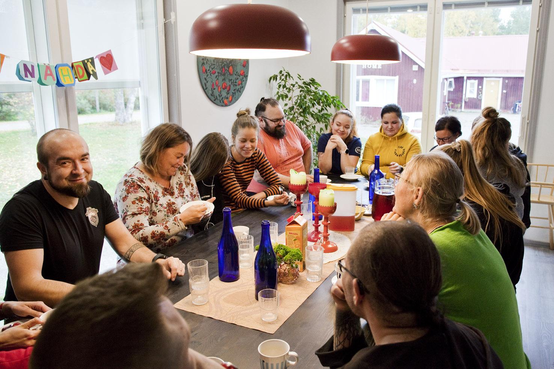Iloinen ryhmä kahvipöydän ääressä